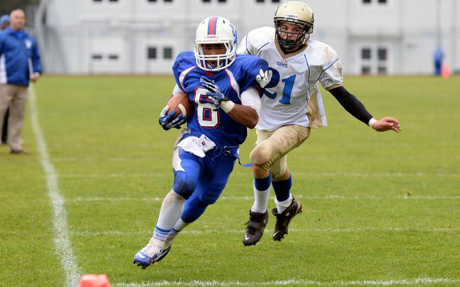 Ramstein's Robert Navarro races Wiesbaden's Johnathan Skeesick to the end zone for Ramstein's third touchdown of the day as Ramstein beat the visiting Warriors Saturday, Oct. 12, 2013, 20-7