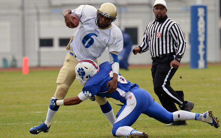 Ramstein's Robert Navarro, right, gets a hold on Reymoi Lewis after the Wiesbaden quarterback picked up some yardage.T he Royals beat Wiesbaden 20-7, Saturday, Oct. 12, 2013.