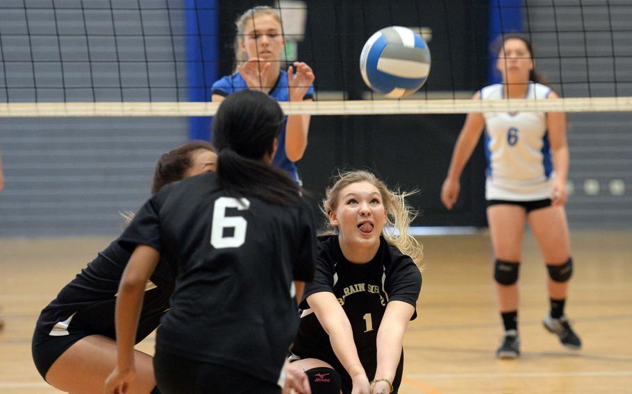 Bahrain's Krista Flores digs deep to try to return a Rota ball as teammates Jacklyn Payne, left, and Madison Belknap get in on the action, while Rota's Tayla Irby and Hailey Landry watch from across the net. Rota won the Division II game on opening day action at the DODDS-Europe volleyball championships, 25-13, 25-11.