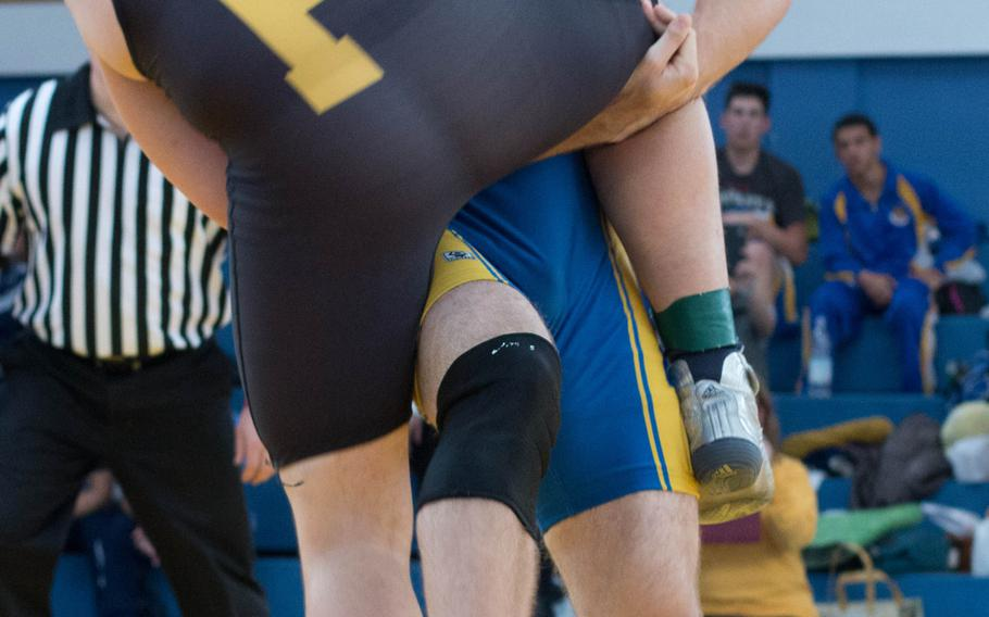 Joshua Pleake from Ansbach High struggles to lift Patch wrestler Matthew Cass during their first round match. Pleake ended up winning that match and ultimately second place in the 182-pound weight class.