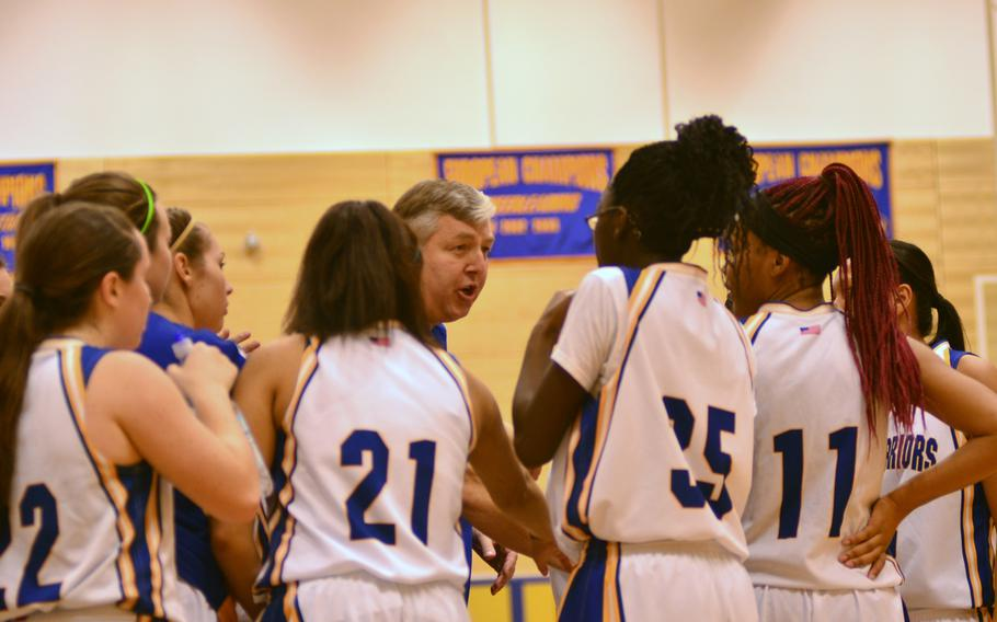 Jim Campbell, head coach of the Wiesbaden Warriors, discusses strategy with his team during a timeout.  The Lady Warriors went on to defeat the Red Raiders in overtime, 45-39.