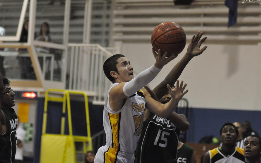 Vicenza's Mario Molina drives in for a basket Friday night and gets tangled with Naples' Juwon English.The Cougars blitzed the Wildcats 64-23.