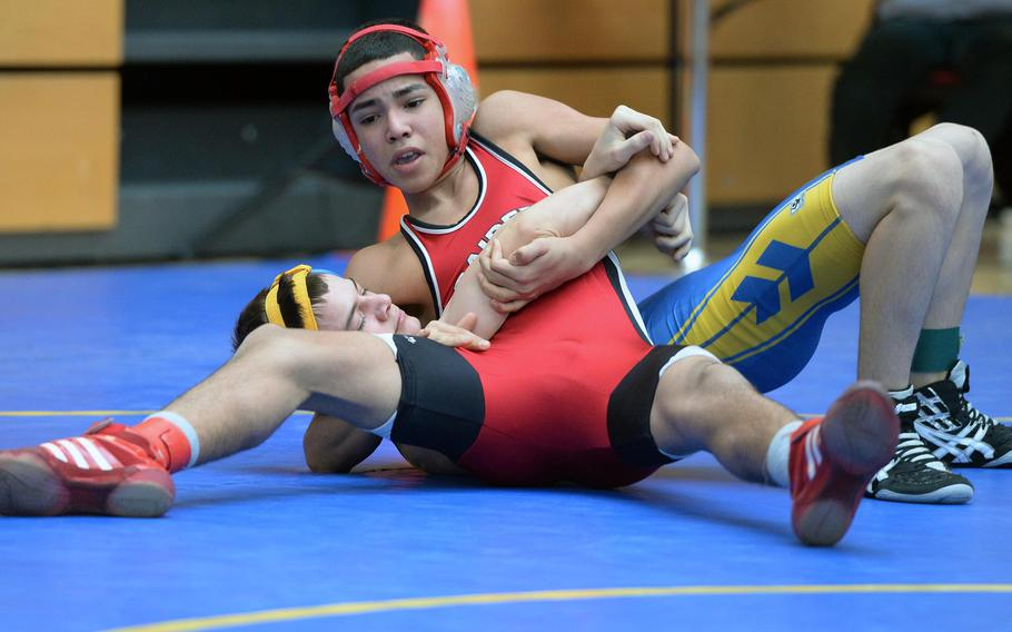 Kaiserslautern's Carlos Muniz, top, beat Ansbach's Jordan Lennon in a 113-pound match in first round action on the first day of the DODDS-Europe wrestling championships in Wiesbaden, Germany, Friday, Feb. 14, 2014.
