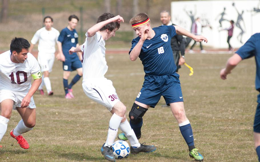 Ramstein's Travis McCloskey threads the ball through half of Vilseck's midfielders during the DODDS-Europe Division I soccer opener, Mar. 21, 2015. Vilseck came away with the victory, 2-1 over the visiting Royals.