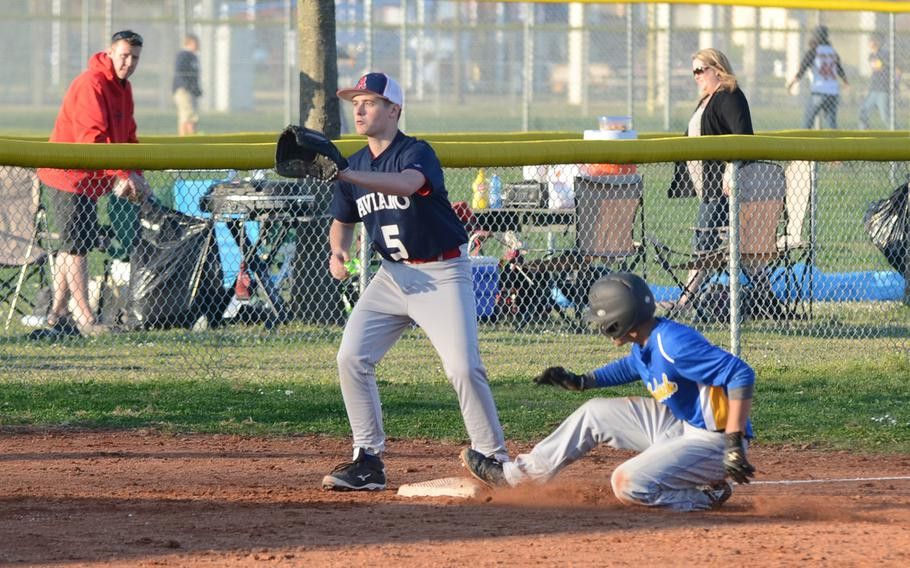 Ansbach's Yadial Rodriguez slides in to third, while Aviano's Nicolas Routier looks for the throw from home plate Saturday at Aviano Air Base, Italy. Ansbach won 10-7.