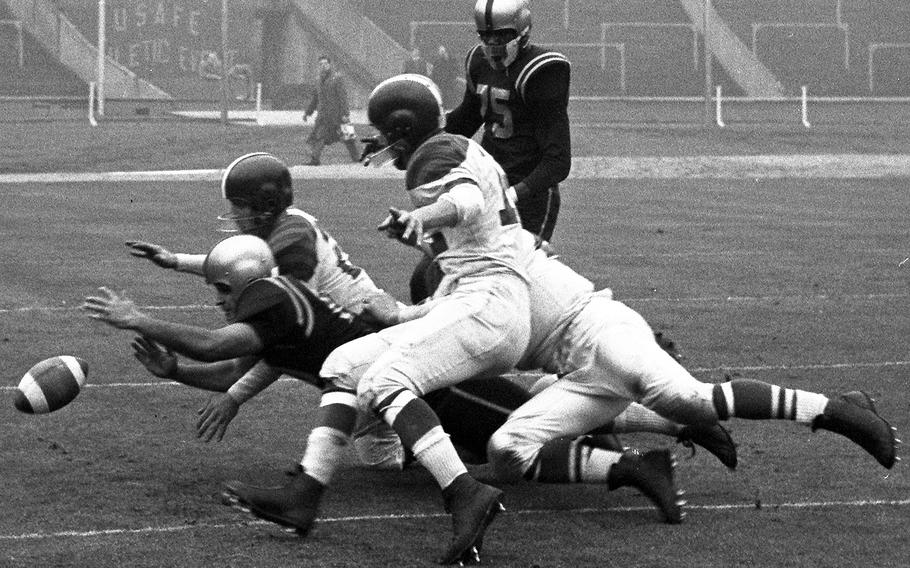 Danny Fuller of the London Rockets (at left, in dark jersey) and three Wiesbaden Flyers players dive for a loose ball during the United States Air Forces in Europe football championship game at London's famed Wembley Stadium in 1956. London won its third straight USAFE title, 32-7.