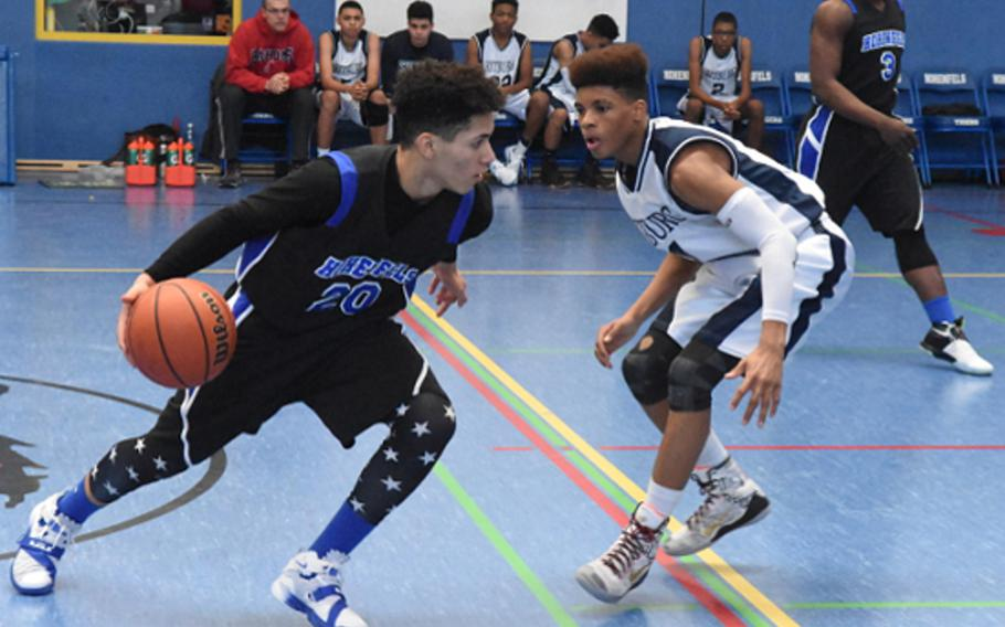 Hohenfels' Jeremy Serrano charges past Bitburg's Deon Montgomery during a DODEA-Europe boys basketball game Saturday.