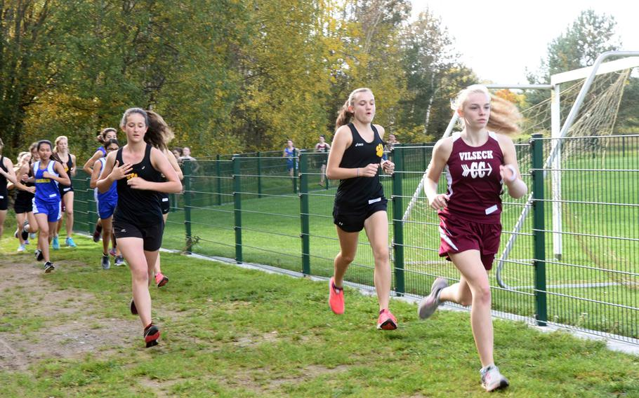 Vilseck's Emma Thompson runs with a cast on her broken arm ahead of two Stuttgart foes at the cross country race at Vilseck, Germany, Sat., Oct. 14, 2017.