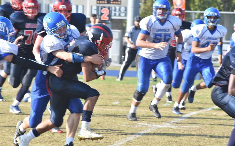 Aviano's Mickey Moore carries Rota's Kaleb Helvey for a few yards Saturday in the Saints' 33-30 victory over the Admirals.