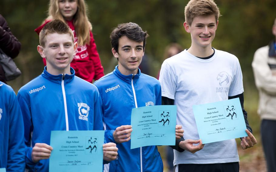 Black Forest Academy's Mac Roberts, right, and Ramstein's Dash Rogers and  Denver Dalpias hold their certificates after a cross country meet in Ramstein-Miesenbach, Germany, on Saturday, Oct. 21, 2017. Roberts won the race with a time of 16:12, Rogers finished second at 16:42 and Dalpias took third place at 17:34.