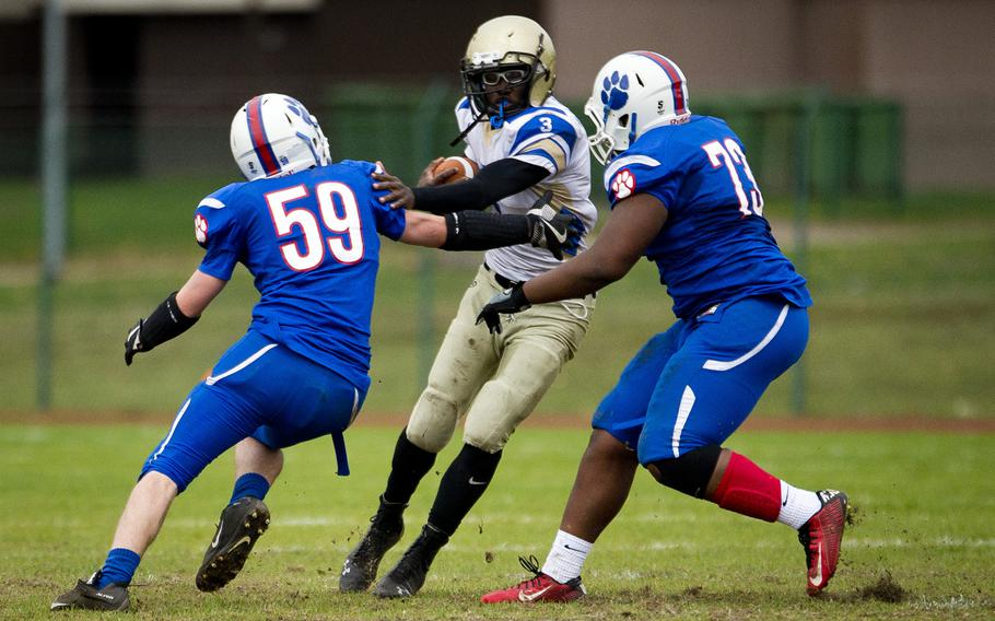 Wiesbaden's Caleb Brown tries to get through Ramstein's Kyle Lloyd, left, and Clifford Jackson during the DODEA-Europe Division I semifinal at Ramstein Air Base, Germany, on Saturday, Oct. 28, 2017.