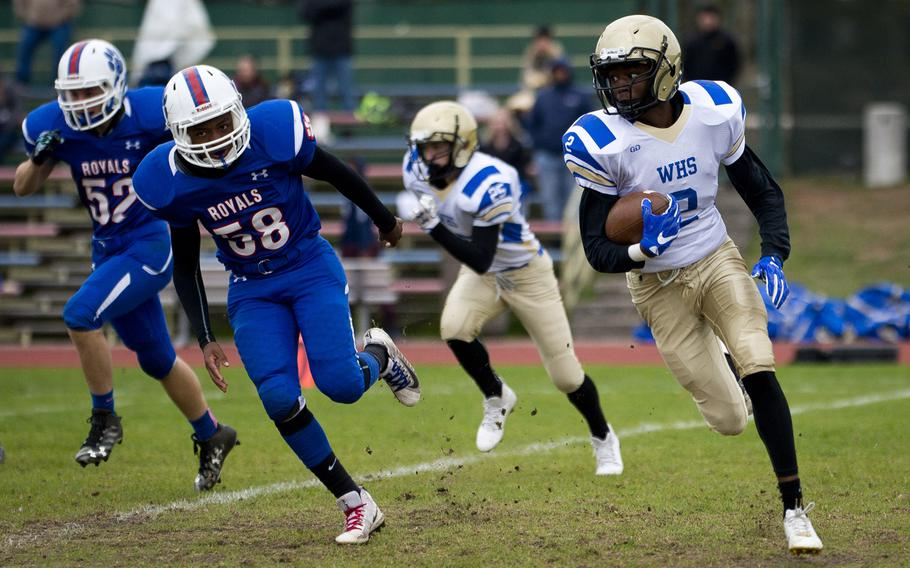 Wiesbaden's Dante Hurt, right, tries to run around Ramstein's Jalon Lewis during the DODEA-Europe Division I semifinal at Ramstein Air Base, Germany, on Saturday, Oct. 28, 2017. Wiesbaden lost the game 13-6.