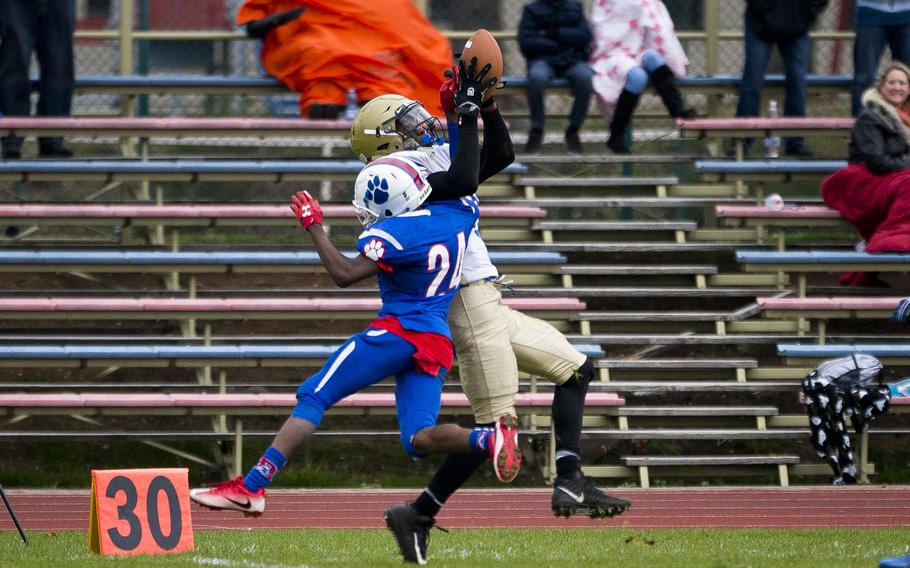 Wiesbaden's Sam Edwards catches a pass over Ramstein's Cameron Chester during the DODEA-Europe Division I semifinals at Ramstein Air Base, Germany, on Saturday, Oct. 28, 2017. Wiesbaden lost the game 13-6.