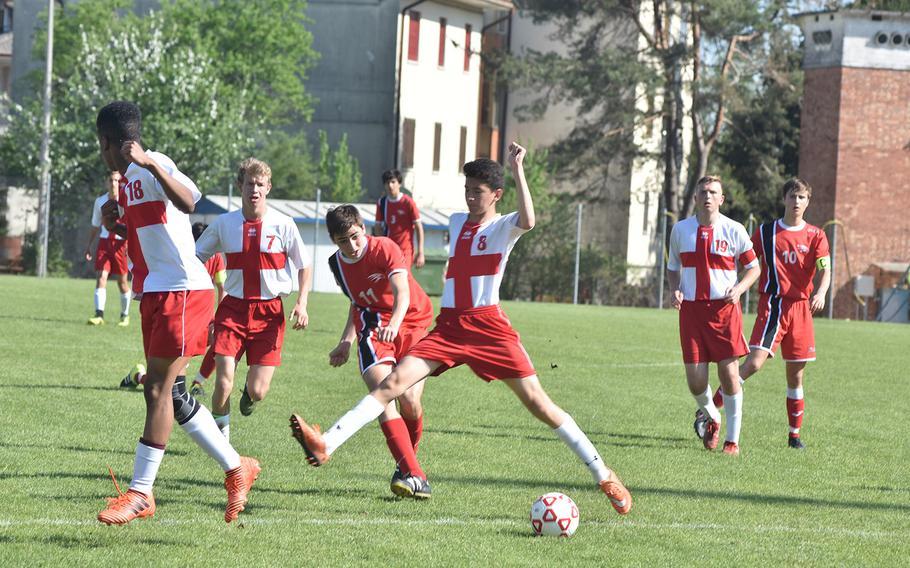 American Overseas School of Rome's Tomasso Anticoli kicks the ball through the outstretched legs of Aviano's Zachary Villa on Saturday, April 21, 2018.