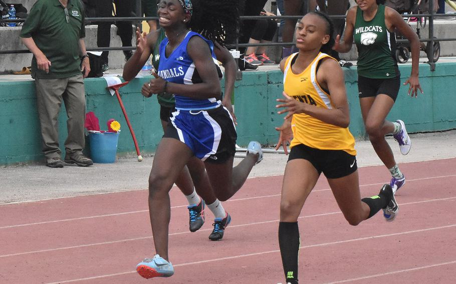 Vicenza's Kaiah Hicks edges past Rota's Erica Tobin in the final stretch of the 200 during a track meet at Naples Middle High School in Gricignano, Italy.
