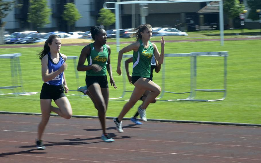 Sprinters from SHAPE and Brussels lead the pack in the 100-meter dash event during a high school track meet at RAF Lakenheath, England, Saturday, May 19, 2018. SHAPE runner Alexia Tarvis earned first place with a 13.21 second finish.