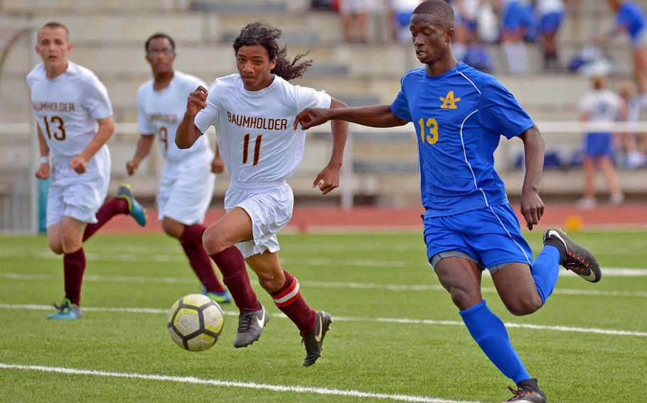 Ansbach's Kevin Kamara pushes the ball upfield against Baumholder's Demauriay Medina in Division III action at the DODEA-Europe soccer finals in Kaiserslautern, Germany, Monday, May 21, 2018. The Cougars beat the Bucs 7-0.