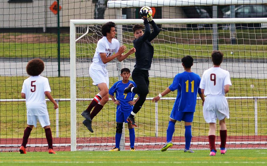Ansbach keeper Nick Benson pulls in the ball against Baumholder's Brandon Perales in a Division III game at the DODEA-Europe soccer finals in Kaiserslautern, Germany, Monday, May 21, 2018. Ansbach won 7-0.