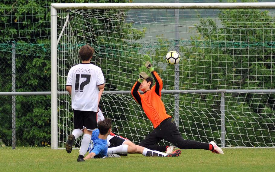 Marymount's Alexander Herne, blue jersey, scores his team's fourth goal as AOSR's Arnaldo Di Biase watches in a Division II semifinal at the DODEA-Europe soccer finals in Reichenbach, Germany, Wednesday, May 23, 2018. Marymount won 4-2 to advance to Thursday's final.