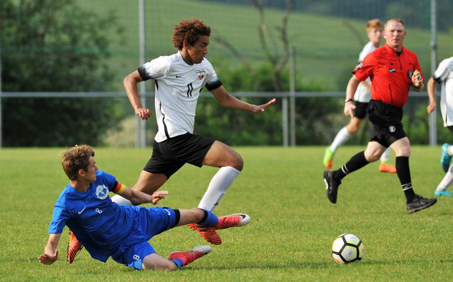 Stuttgart's Gustavus de Andrade avoids the tackle by Ramstein's Gregory McMillan in a Division I semifinal at the DODEA-Europe soccer finals in Reichenbach, Germany, Wednesday, May 23, 2018. Stuttgart beat Ramstein 1-0 to advance to Thursday's division final against Kaiserslautern.