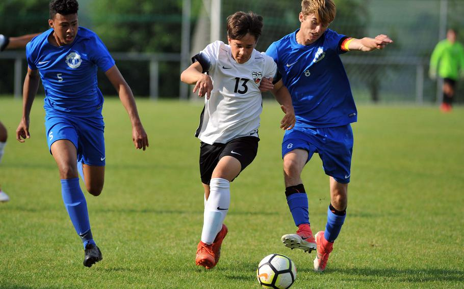 Stuttgart's Tanner Balisky battles for the ball with Ramstein's Gregory McMillan in a Division I semifinal at the DODEA-Europe soccer championships in Reichenbach, Germany, Wednesday, May 23, 2018. Stuttgart beat Ramstein 1-0 to advance to Thursday's final. At left is Ramstein's Noah Yancy.