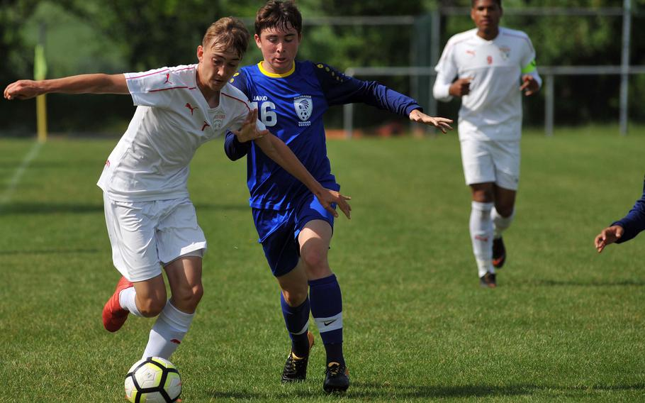 Kaiserslautern's Phillip Rimmler, left and Wiesbaden's Timothy Worthington battle for the ball in a Division I semifinal at the DODEA-Europe soccer finals in Reichenbach, Germany, Wednesday, May 23, 2018. Kaiserslautern beat the Warriors 4-1 to advance to Thursday's division final.