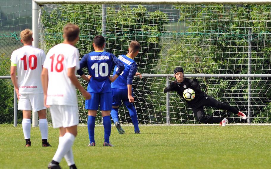 Kaiserslautern goalie Enrico Art stops a penalty shot by Wiesbaden's Anthony Hall in a Division I semifinal at the DODEA-Europe soccer finals in Reichenbach, Germany, Wednesday, May 23, 2018. Kaiserslautern beat the Warriors 4-1 to advance to Thursday's division final.