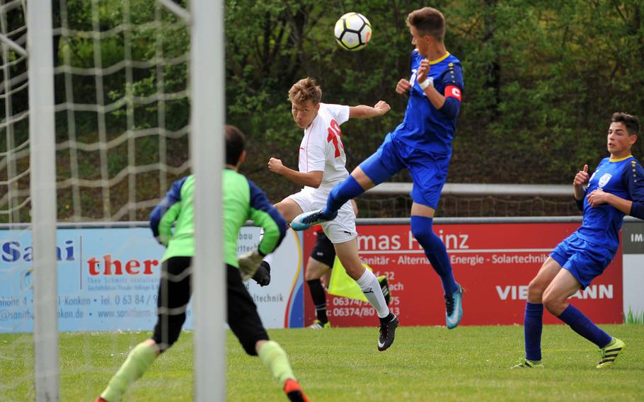 Kaiserslautern's Chris Christansen centers the ball as Wiesbaden's keeper Matias Chavez and his backfield defends in a Division I semifinal at the DODEA-Europe soccer finals in Reichenbach, Germany, Wednesday, May 23, 2018. Kaiserslautern beat the Warriors 4-1 to advance to Thursday's division final.