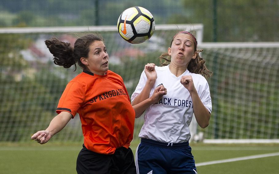Spangdhalem's Summer Flores, left, and Black Forest Academy's Rebecca Losey jump for the ball during the DODEA-Europe soccer championships in Reichenbach, Germany, on Wednesday, May 23, 2018.