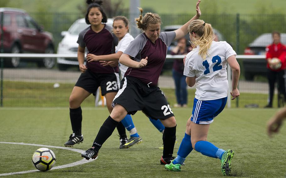 Rota's Hailey Gruetter, right, gets a shot off past AFNORTH's Jeanna Barrick during the DODEA-Europe soccer championships in Reichenbach, Germany, on Wednesday, May 23, 2018. Rota won the Division II semifinal match 3-1.