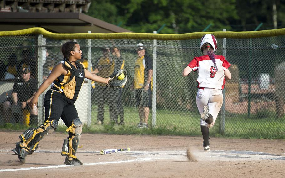 Kaiserslautern's Chloe Whisennand, right, runs past Vicenza's Lauren Miller to score during the DODEA-Europe softball tournament in Kaiserslautern, Germany, on Friday, May 25, 2018.  Kaiserslautern won the Division I game against Vicenza 14-0 and advances to the semifinals.