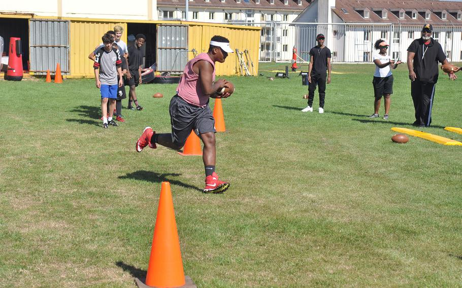 Baumholder senior Jeremiah Christopher catches a pass from head coach Phillip Loyd in a preseason football drill. The all-conference lineman will face a major adjustment as the Bucs convert from 11-man to six-man football this fall.