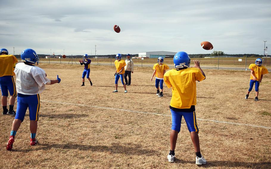 The Ansbach Cougars pass footballs during practice, Monday, August 27, 2018.