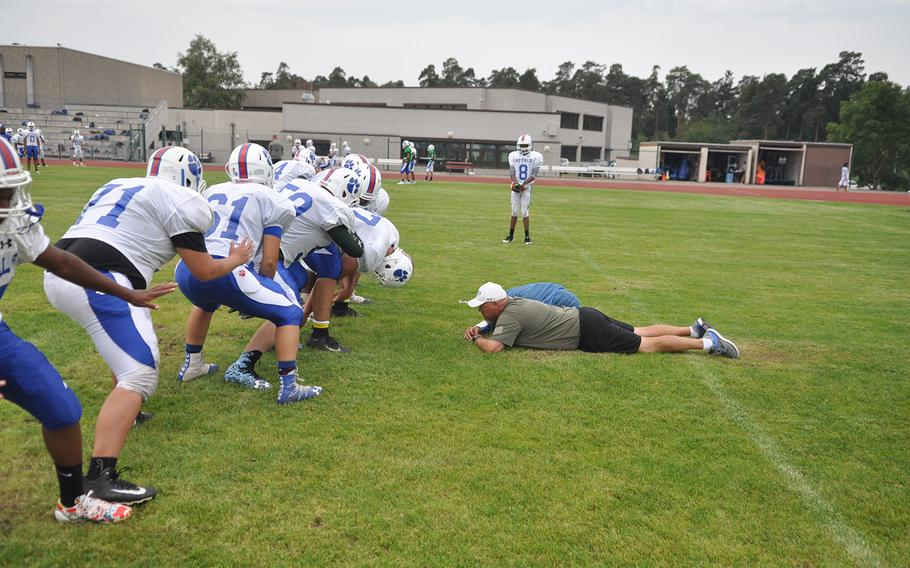 Ramstein Royals head coach Carter Hollenbeck gets a close look at a placekicking drill at a preseason practice session at Ramstein Air Base, Germany. Hollenbeck leads a coaching staff that has worked together for multiple seasons.