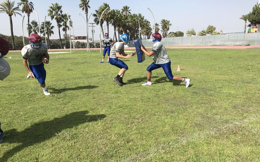 Rota Admirals players collide in a preseason football practice at Rota, Spain. The Admirals have played in every Division II championship game since 2015, including a win in 2016.