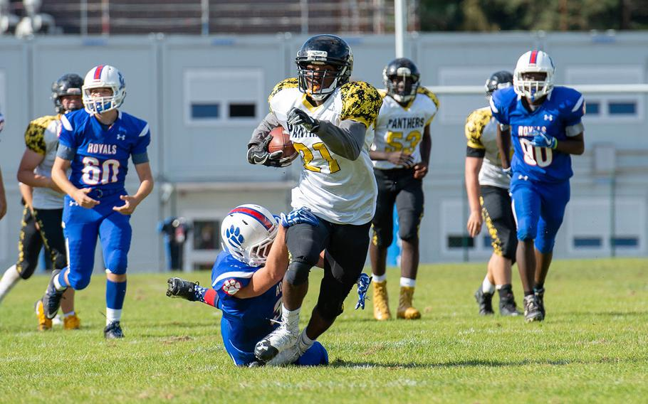 Gavin Abney tries to break a tackle to pick up a few extra yards during the Ramstein vs Stuttgart football game on Saturday, Sept. 15, 2018.  Ramstein won the game 41-19.