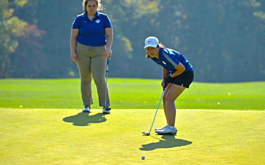 Ramstein's Phoebe Shin watches her ball head toward the cup on the ninth hole during first-day action at the DODEA-Europe golf championships at Rheinblick golf course in Wiesbaden, Germany, Wednesday, Oct. 10, 2018. Watching is teammate Lauren Sutherland.