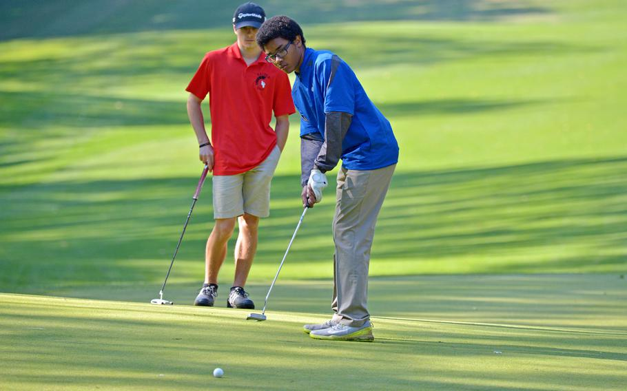 Ramstein's Ben Todman follows his ball to the cup as Kaiserslautern's George Stephan watches on the first day of competition at the DODEA-Europe golf championships at Rheinblick golf course in Wiesbaden, Germany, Wednesday, Oct. 10, 2018.