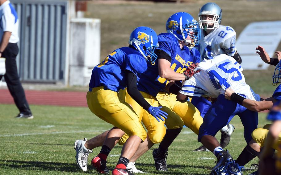 A group of Ansbach Cougars stop Brussels' Kimouri Vaughan, right, during a game at Ansbach, Germany, Saturday, Oct. 13, 2018.