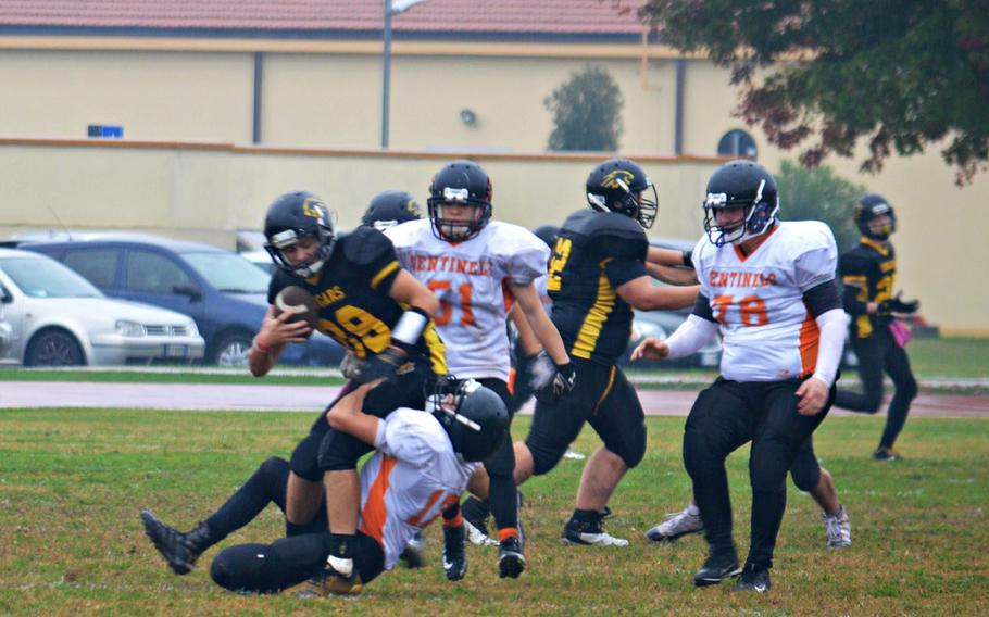 Tyler Keller, a defensive end with the Spangdahlem Sentinels, tackles Jesse Samsel, a quarterback with the Vicenza Cougars. Vicenza defeated Spangdahlem 39-3 in Saturday's rainy game.