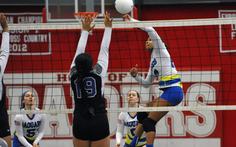 Sigonella's D'Anna Holland punches the ball across the net against Yosleen Alokoa of Hohenfels in a Division III match at the DODEA-Europe volleyball finals in Kaiserslautern, Germany, Thursday, Nov. 1, 2018.  The Jaguars won 25-13, 25-17, 25-5.