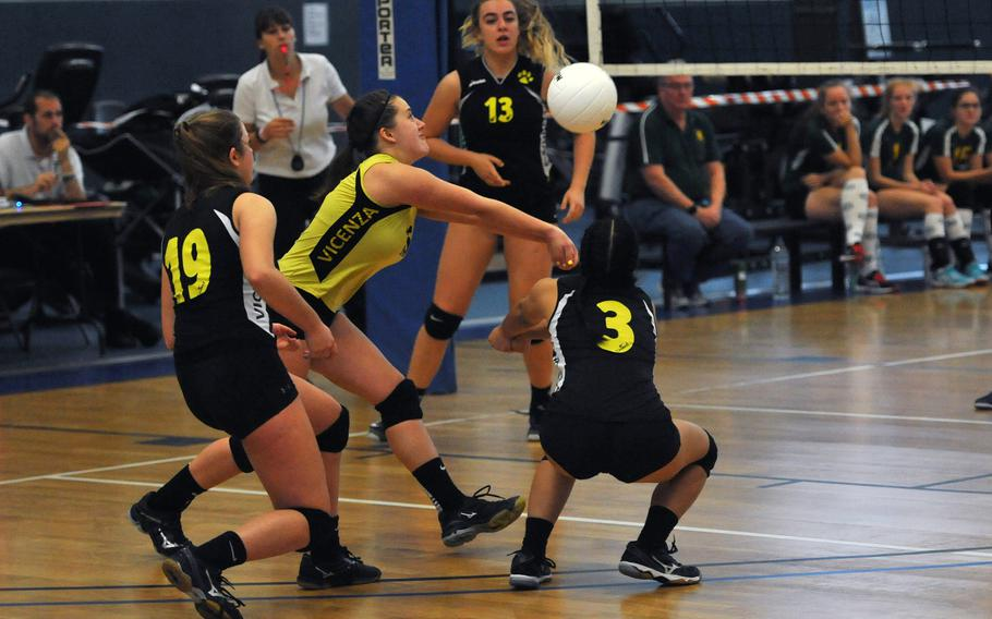 Surrounded by teammates, Vicenza libero Emilee Deck returns the ball in the Cougars' 25-12,25-22,25-13 win over SHAPE on the first day of action at the DODEA-Europe volleyball finals in Kaiserslautern, Germany, Thursday, Nov. 1, 2018.