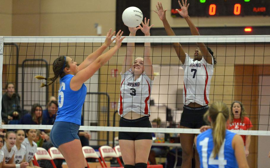 Marymount's Margherita Guerra slips the ball between the block of Aviano's Elizabeth Woodruff, left, and Layla Thomas in her team's 25-23, 23-25,25-19, 22-15, 15-11win over the Saints in a Division II semifinal at the DODEA-Europe volleyball finals in Kaiserslautern, Germany, Friday, Nov. 2, 2018.