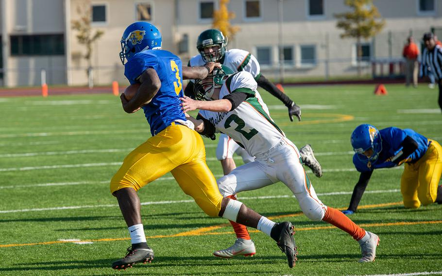 Ogden Andrew from Ansbach stiff arms a defensive player during the DODEA-Europe Division III football championship game between the Ansbach Cougars and AFNORTH Lions, Saturday, Nov. 3, 2018.