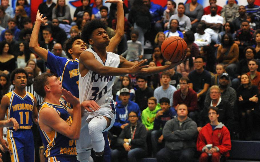 Ramstein's Jerod Little goes in for a shot past Wiesbaden's Roberto Eiseman, left, and Dom Bivins in a game at Ramstein Tuesday, Dec. 4, 2018. Ramstein won the game 67-61.