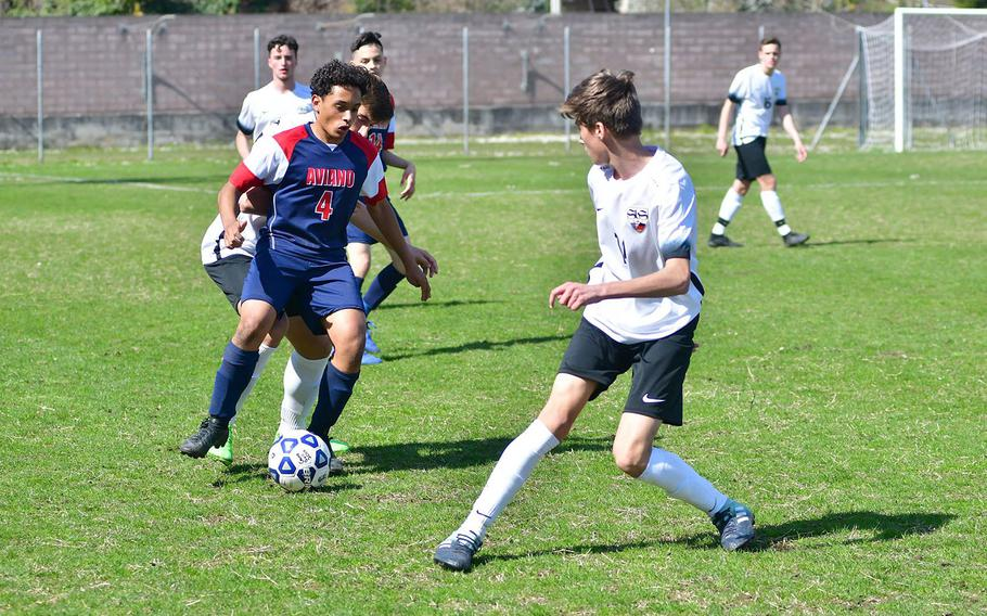 Nicholas Gilbert of the Aviano Saints attempts to get by Stuttgart defenders during Saturday's game, which was played at the Aviano stadium. Despite playing well, the Aviano Saints lost the game 2-0.