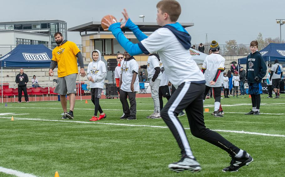 Lucas Hollenbeck, 12, receives a pass from Pittsburg Steelers offensive lineman Alejandro Villanueva during a pro camp at Kaiserslautern High School football field Saturday, April 13, 2019. More than 200 kids from around Germany attended the two-day football camp.