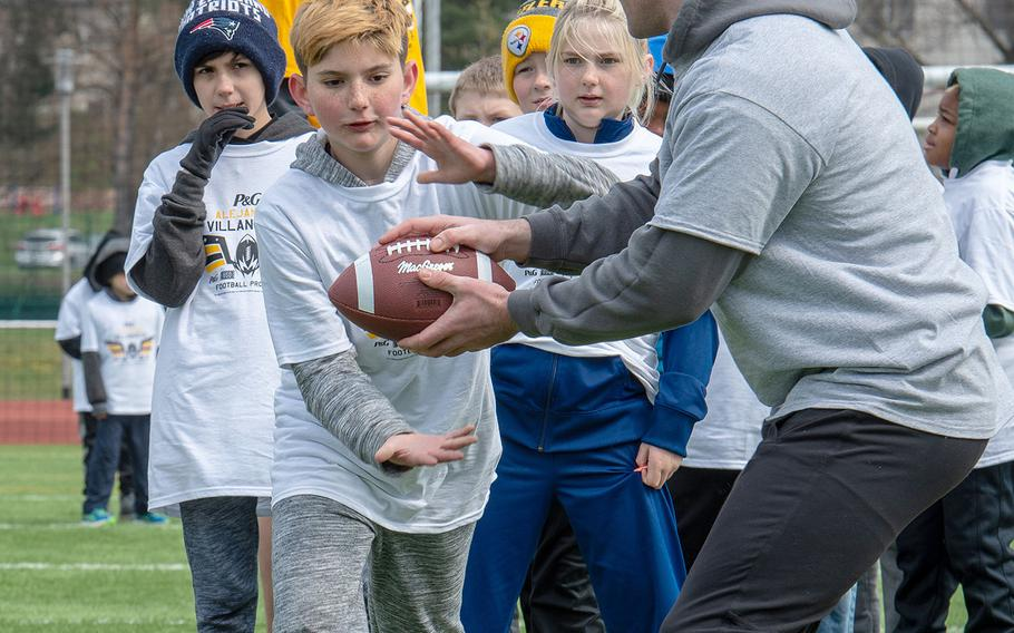 A pro camp participant takes a handoff during a drill at Kaiserslautern High School football field Saturday, April 13, 2019. More than 200 kids from around Germany attended the two-day football camp.