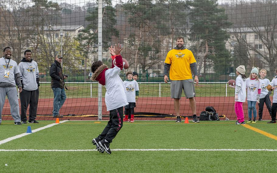 Pittsburg Steelers offensive lineman Alejandro Villanueva passes the ball to a young receiver during a pro camp at Kaiserslautern High School football field Saturday, April 13, 2019. More than 200 kids from around Germany attended the two-day football camp.
