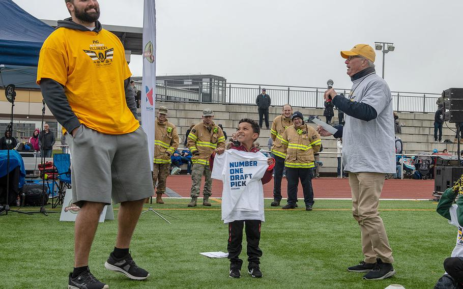 Pittsburg Steelers offensive lineman Alejandro Villanueva presents Khlil Mackey, 6, with the number one draft pick t-shirt before a pro camp at Kaiserslautern High School football field Saturday, April 13, 2019. More than 200 kids from around Germany attended the two-day football camp.